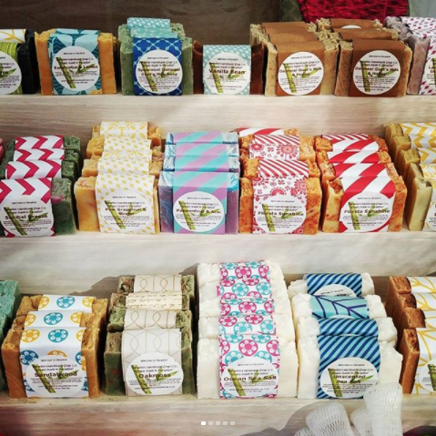 Rows of soap with labels on shelves, by Paradise Handmade Soap.