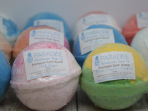 Fizzy Bath Bombs by Paradise Handmade Soap. 3 rows of colorful bath bombs with labels.